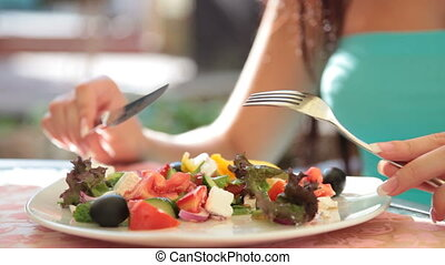 Greek salad - unrecognizable young woman has dinner in...