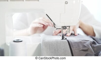 Unrecognizable young woman s hands sewing at a sewing machine