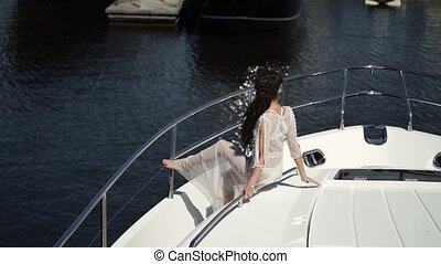 Unrecognizable young woman sitting on yacht