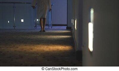 Unrecognized woman dressed in bathrobe walk in the dark hotel corridor