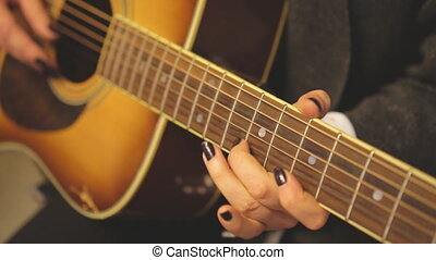 Unrecognized woman musician playing on the guitar.