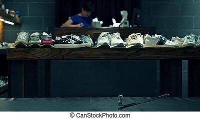 Unrecogrizable shoes shop assistant at work video