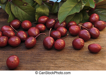 Unripe red plums on a wooden table