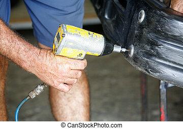 Car mechanic screwing or unscrewing car bumper with oil pressure gun
