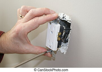 unscrewing household outlet - electrician taking outlet from...