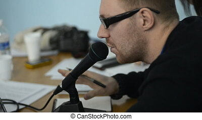 Unshaven man in glasses speaks into the microphone