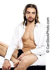 unshaven - Handsome man in an unbuttoned white shirt sitting...