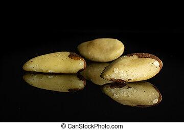 Group of three whole fresh unshelled brazil nut isolated on black glass