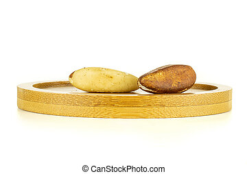 Group of two whole unshelled brazil nut on bamboo plate isolated on white background