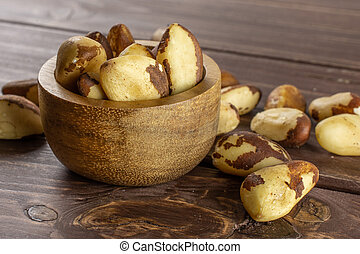 Lot of whole unshelled brazil nut near and in wooden bowl on brown wood