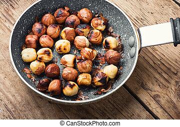 Pile of roasted peeled hazelnuts.Hazelnut fried in a frying pan