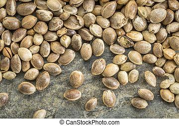 close up background of unshelled hemp seeds on a slate stone