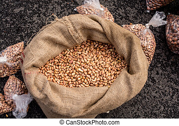 Unshelled peanuts in a straw sack in the view