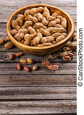 Unshelled peanuts in wooden bowl