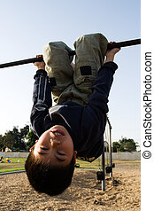 Unside down kid - Young asian boy hanging upside down on a...