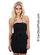Unsmiling blonde model in black dress posing looking at...
