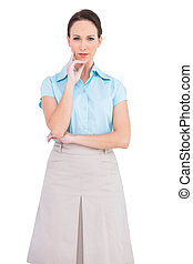 Unsmiling classy businesswoman posing on white background