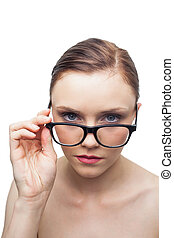 Unsmiling clean model looking over her classy glasses