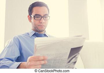 Unsmiling man reading a newspaper