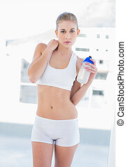 Unsmiling young blonde model holding a water bottle