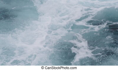 A birds eye view shot of the ocean's water on an unstable waters