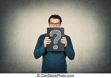 Unsure businessman looks to camera, holding a board with a drawn interrogation mark isolated on grey wall background. Business worker wearing glasses, has questions. Introvert personality concept.