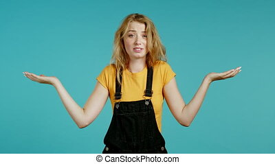 Unsure woman in overall shrugs her arms, makes gesture of I don't know, care, can't help anything . Girl on blue background