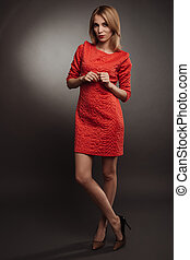 Unsure young blonde business woman in red dress