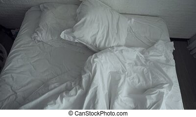 Untidy crumpled bed with white bedclothes. - Top view on ...