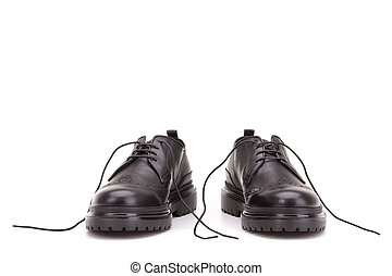 Untied shoelaces in black shoes. A pair of boots on a white background.