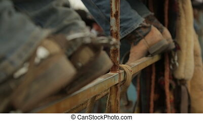 Untying a rope on a metal rod and cowboy shoes - A hand held...