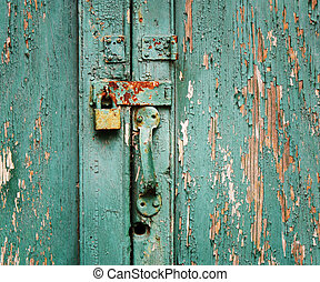 Rusty, unused lock on an old wooden door with peeling paint.