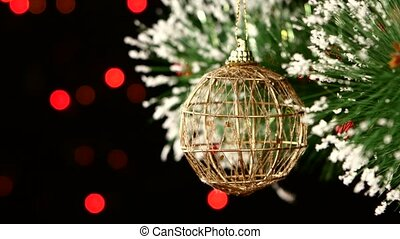 Unusual decoration - a round brown toy on christmas tree, bokeh, light, black, garland