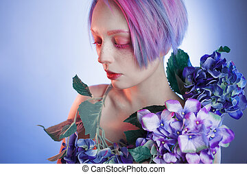unusual girl with blue flowers, focus on flower - a young...