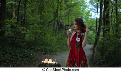 Unusual girl with creative make-up holding burning candle in the dark forest