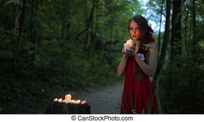 Unusual girl with creative make-up holding two burning candles in dark forest