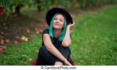 Unusual hipster woman with blue dyed hair sitting near trees in apple garden at autumn season. Girl smiling to camera. Organic, nature concept. High quality FullHD footage