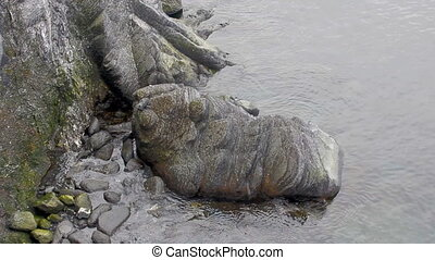 Unusual huge stone is rolled water at base cliffs of Novaya...