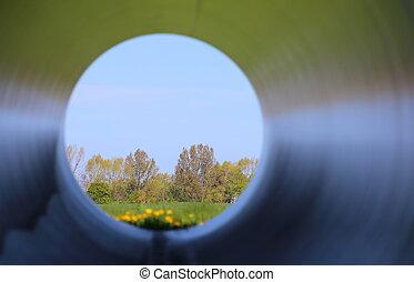 Unusual look through a big steel pipe.