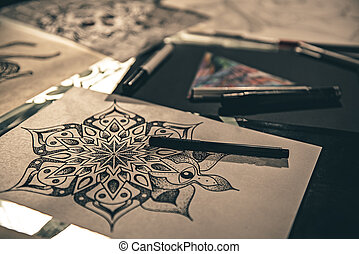 Unusual sketches of tattoo locating on desk
