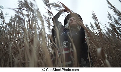 Unusual stylish woman dancing among reeds swaying in wind. Late autumn nature concept. Attractive trendy girl. Authentic gypsy footage . High quality 4k footage
