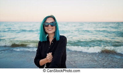 Unusual woman with blue dyed hair dancing, spinning hands around on sea background. Femininity, vacation, vitality, healthy living concept. Girl having fun, laugh. FullHD footage.