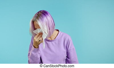 Unusual woman with purple hair sneezes into tissue. Isolated on blue studio background. Girl is sick, has a cold or allergic reaction. Coronavirus, epidemic 2020, illness concept.