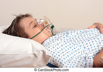A child resting wearing a patient gown has an oxygen mask or inhaler over face.