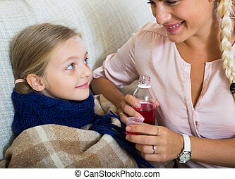 Unwell little girl taking mixture from worried mother - ...