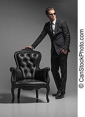 uomini, con, chair., piena lunghezza, di, fiducioso, giovane, uomini affari, in, occhiali da sole, standing, appresso, il, vendemmia, sedia, mentre, isolato, su, grigio