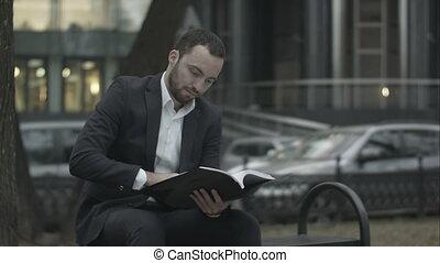 uomo, è, seduta, su, uno, panca, parco, e, dispiaciuto, lettura, pianificazione aziendali