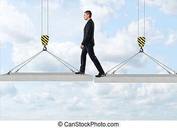 uomo affari, è, avanzando, sopra, uno, divario, da, uno, concreto, pannello, a, un altro, aria, su, il, fondo, di, il, cielo