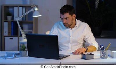 uomo affari, con, laptop, e, carte, notte, ufficio