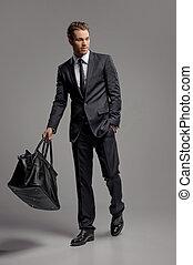 uomo affari, con, suitcase., piena lunghezza, di, fiducioso, giovane, uomini affari, in, portante, uno, valigia, mentre, isolato, su, grigio